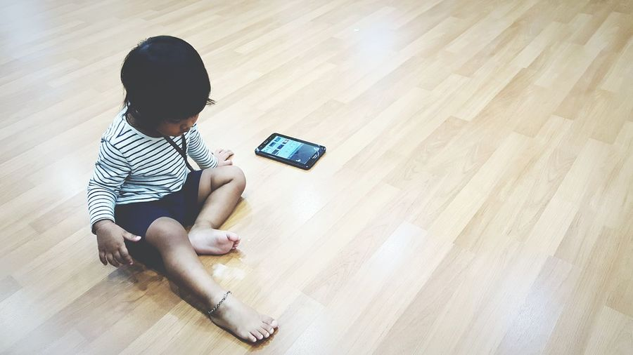 High angle view of boy sitting on hardwood floor