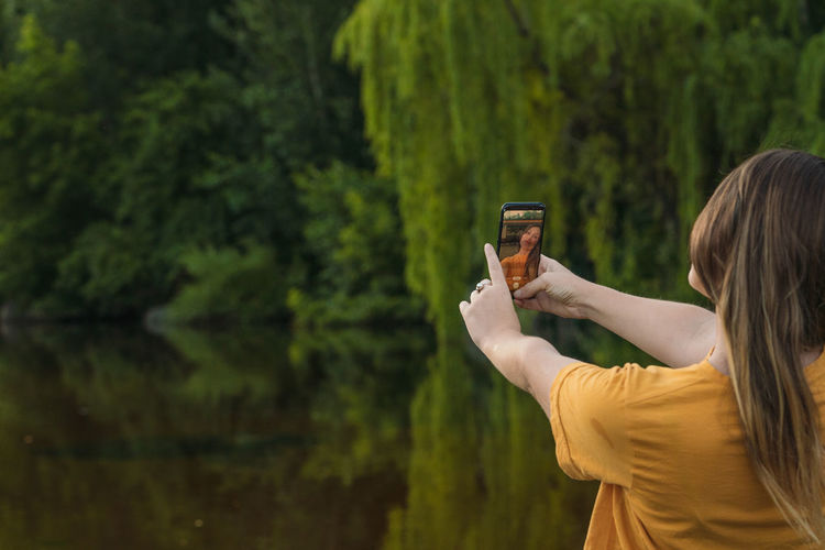 Rear view of woman doing selfie against trees