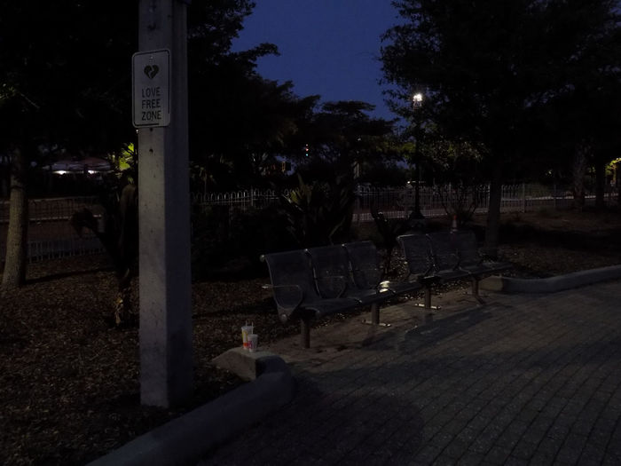 Empty bench in park at night