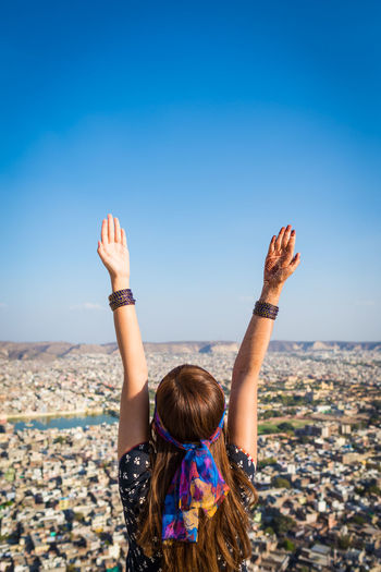 Woman with arms raised standing against townscape