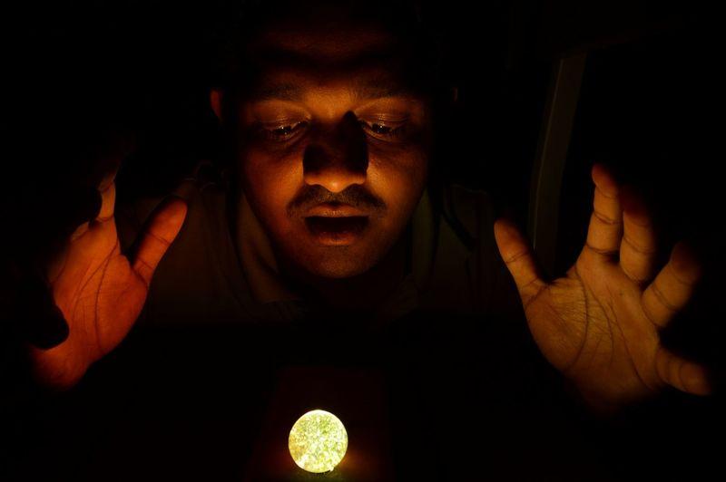 Close-Up Of Man Looking At Illuminated Ball In Darkroom