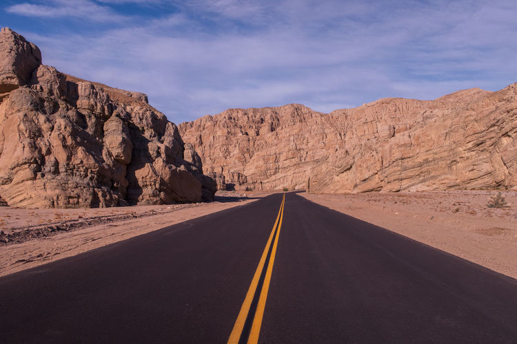 Empty road along rocky mountains against sky
