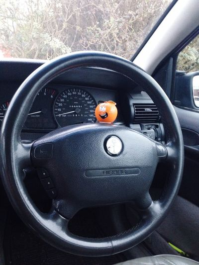 Ornament Orange Color Orange Car Mode Of Transportation Vehicle Interior Motor Vehicle Car Interior Transportation Land Vehicle Indoors  No People Steering Wheel Control Travel Dashboard Control Panel Close-up Glass - Material Gearshift Day Nature
