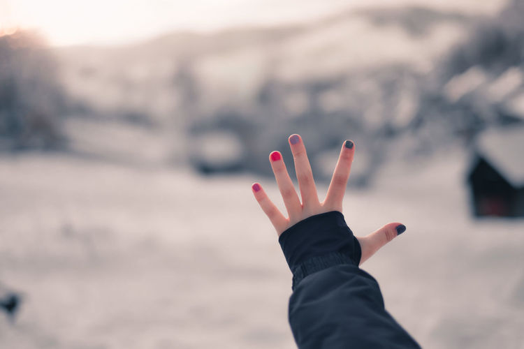Kid showing hand with painted fingernails in front of a winter wonderland lanfscape