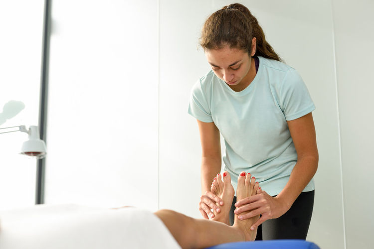 Medical massage at the foot in a physiotherapy center. Female physiotherapist inspecting her patient. Indoors  Adult Women Body Care Healthcare And Medicine Relaxation Human Body Part Lifestyles Holding People Two People Beauty Treatment Waist Up Beauty Spa Healthy Lifestyle Wellbeing Young Adult Beauty Body Care And Beauty Rubbing Responsibility