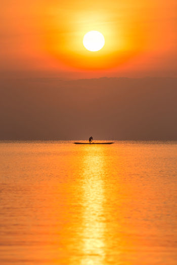 Sunrise and fisherman in the lake. Beauty In Nature Bright Fisherman Horizon Over Water Idyllic Mode Of Transportation Nature Nautical Vessel Orange Color Outdoors Reflection Scenics - Nature Sea Silhouette Sky Sun Sunlight Sunrise Tranquil Scene Tranquility Transportation Water Waterfront