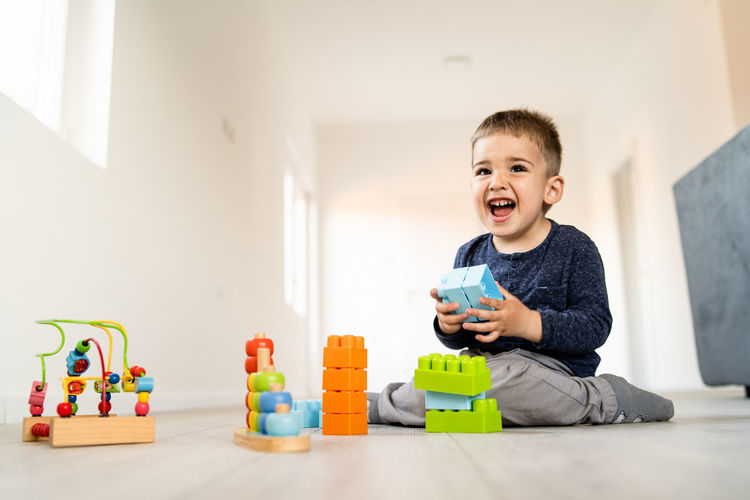 Childhood Child Indoors  Happiness Toy Men Lifestyles Emotion Toy Block Innocence Home Interior Boys Smiling Real People Males  Front View People Multi Colored Leisure Activity Mouth Open