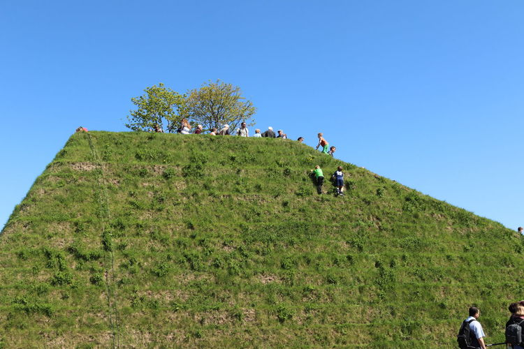Low Angle View Of People On Green Pyramid Against Clear Blue Sky