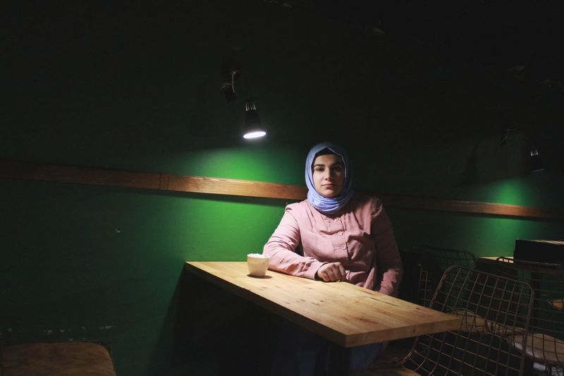 Portrait of woman sitting on table at cafe