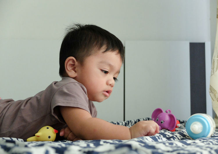 Cute baby boy playing with toys while lying on bed at home