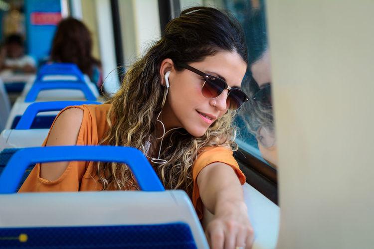 Beautiful young woman sitting in bus