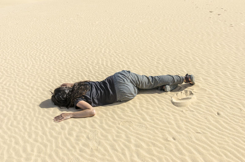 High Angle View Of Woman Lying On Sand At Beach