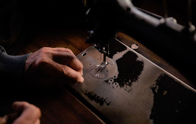 Cropped Hands Of Tailor Using Sewing Machine