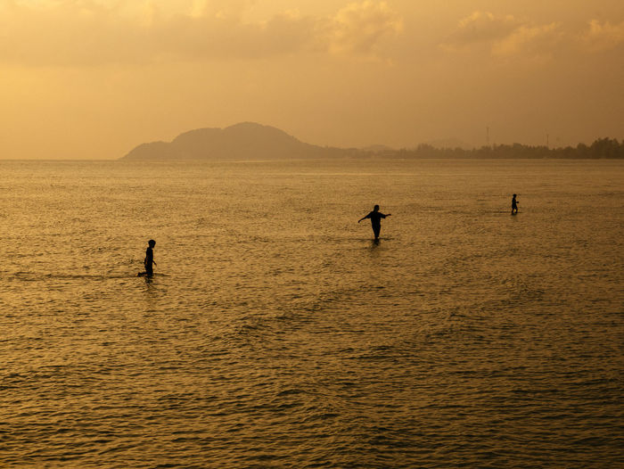 Silhouette people in sea  during sunset