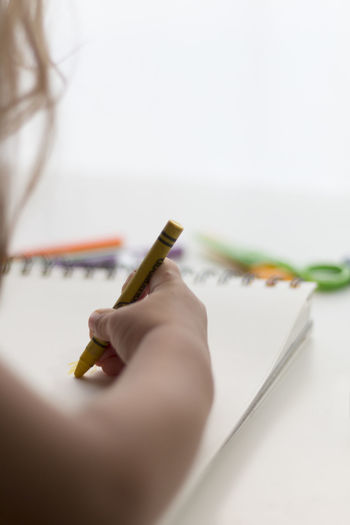 Cropped image of child painting on book with crayon