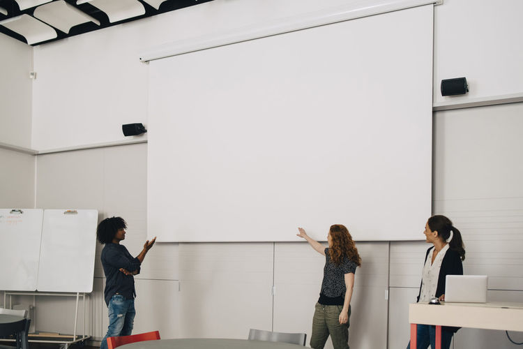 People standing on table against white wall