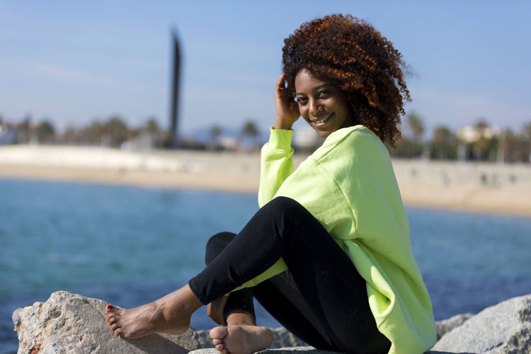 Side view of beautiful curly afro woman sitting on breakwater rocks laughing while looking camera outdoors One Person Sitting Smiling Water Young Adult Women Full Length Lifestyles Happiness Leisure Activity Focus On Foreground Casual Clothing Portrait Young Women Adult Side View Curly Hair Day Hairstyle Beautiful Woman Outdoors Drinking Woman African American Afro Denim Happiness Happy Fun Daylight Sunlight