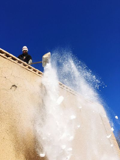 Low angle view of person throwing snow from roof against blue sky