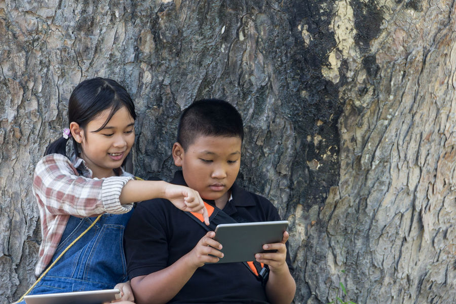 Boys Childhood Communication Concentration Connection Day Digital Tablet Friendship Happiness Holding Internet Learning Leisure Activity Lifestyles Looking Down Outdoors Portable Information Device Real People Sitting Technology Togetherness Touch Screen Two People Using Computer Wireless Technology