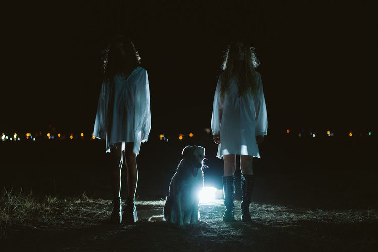 Full length of female friends standing by dog on land at night