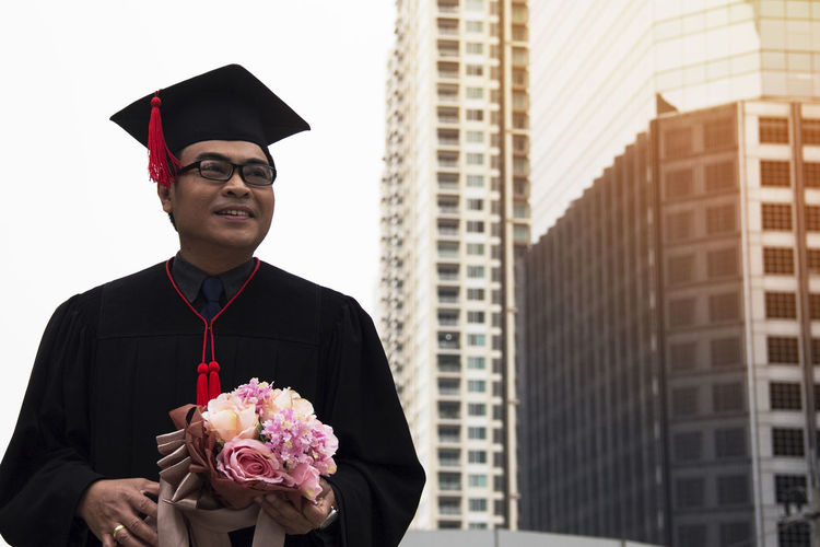 Close-Up Of Man In Graduation Gown Holding Bouquet While Standing At City