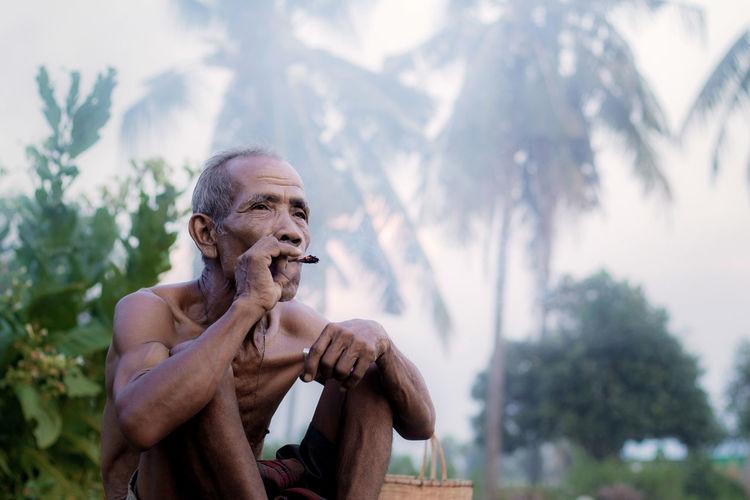 Man looking at camera against trees