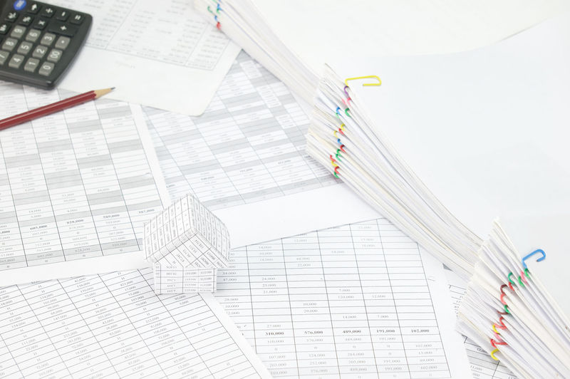 High angle view of model house and calculator on financial documents