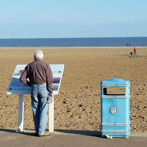 Protect The Environment Wind Turbine Litter At The Beach Environmental Awareness Clean Environment Litter Bin Wrapper The Tourist Wind Farm Offshore Man Holding Bottled Water How Do We Build The World? Climate Change Landscapes With WhiteWall