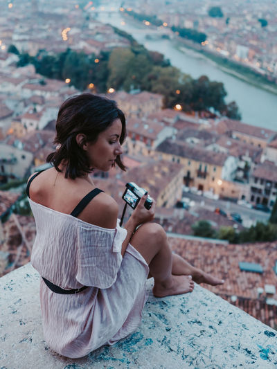 The view over Verona makes for a great portrait location Week On Eyeem One Person Young Adult Lifestyles Leisure Activity Young Women Technology Hairstyle Long Hair Architecture Sitting Photography Themes Women Holding Focus On Foreground Hair Looking Activity Beautiful Woman Outdoors Verona Italy Model Cityscape