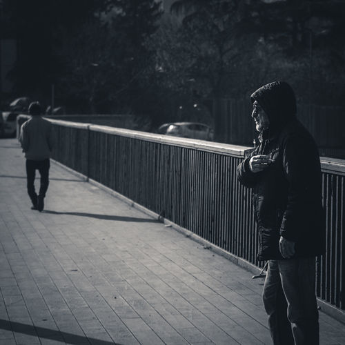 Side view of man and woman walking on footpath