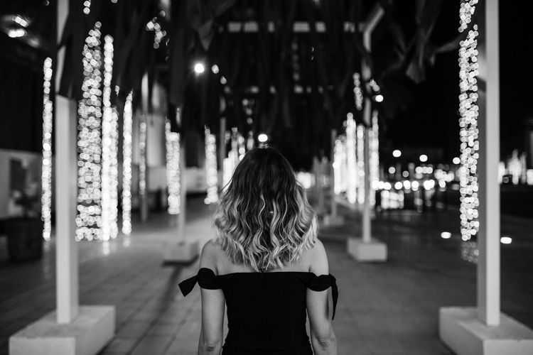 Rear view of woman standing at illuminated night