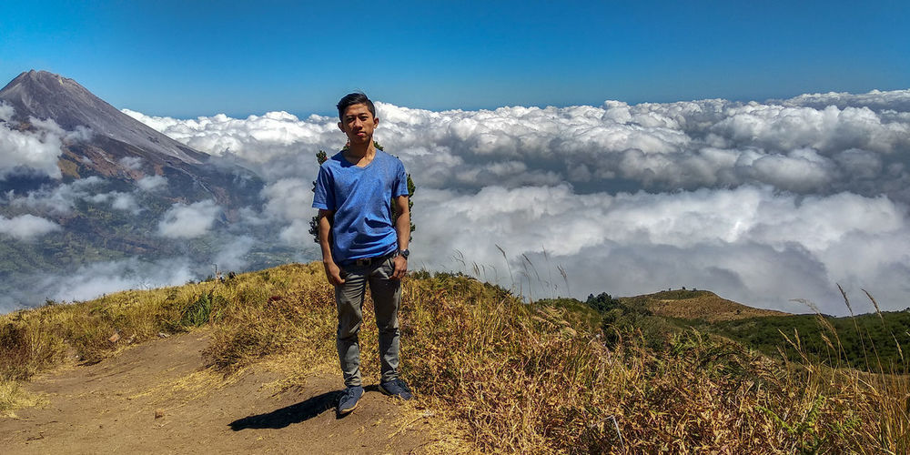 Portrait of man standing against cloudscape on mountain