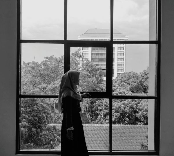 Side view of woman in hijab looking through window