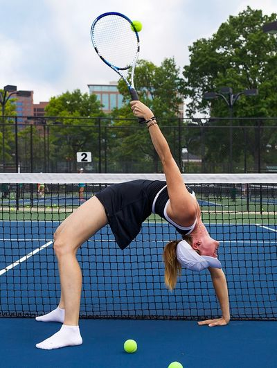 Female Player Doing Backbend While Playing Tennis In Court