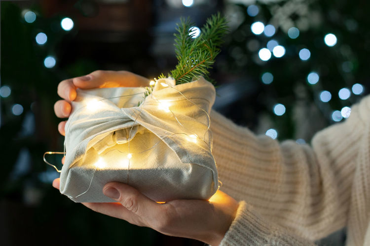 Christmas gift in hands. packaging in eco-friendly materials, furoshiki fabric.