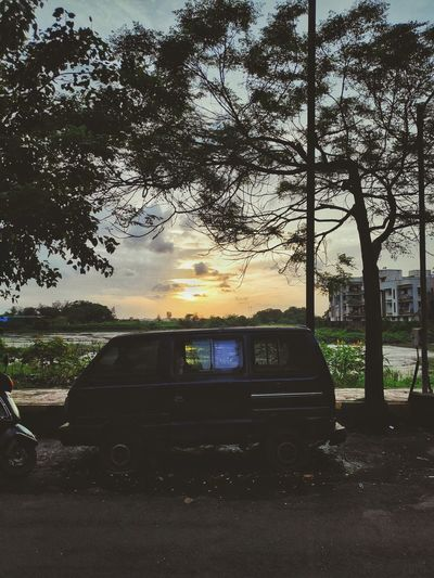 Car on street against sky during sunset