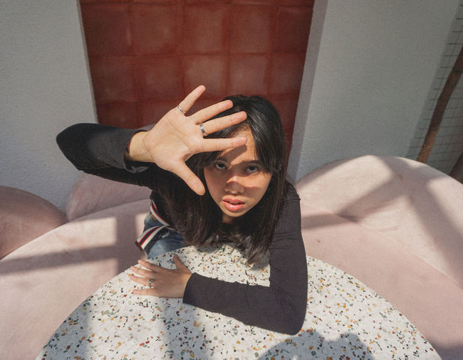 High angle portrait of young woman shielding eyes while sitting at table