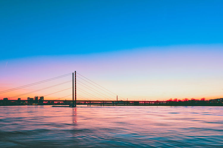 Duesseldorf, GERMANY - March 22, 2019: River Rhine is glooming in the sinking sun and provides a spectatular view on the new media harbor Sky Water Bridge Bridge - Man Made Structure Connection Built Structure Architecture Waterfront Transportation Engineering River Nature Suspension Bridge Blue Sunset Copy Space Beauty In Nature Scenics - Nature Outdoors Bay Purple