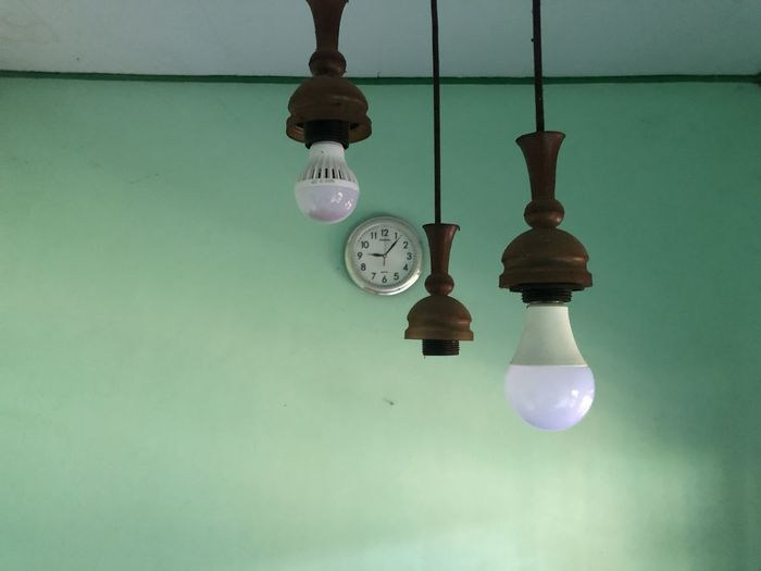 Close-up of light bulb on table against wall