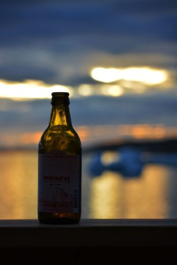 Ilulissat, Greenland - July - enjoying the midnight sun and the view in the disco bay with a bottle of greenlandic beer - Immiaraq Lager Bottle Glass - Material Focus On Foreground No People Water Sunset Sea Iceberg Midnight Midnight Sun Transparent Drink Beverage Relaxation Beautiful Quiet Silence Lonely Travel Destinations Greenland Outdoors Love Life Close-up Orange Color Beer