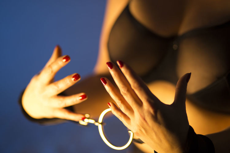 Midsection of woman with handcuffs against blue background