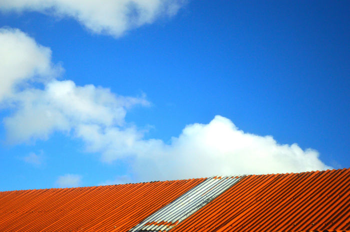 Beauty In Nature Blue Sky Cloud - Sky Day House Low Angle View Nature No People Orange Color Outdoors Rooftop Shed Roof Sky Tiled Roof  Tin Roof White Clouds And Blue Sky