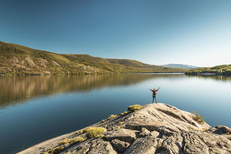 Man standing on rock by lake against clear blue sky