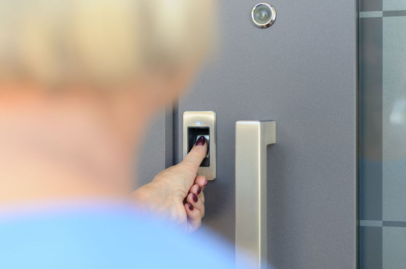 Rear view of senior woman unlocking door from thumb