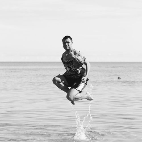 Full length of young man at beach against sky