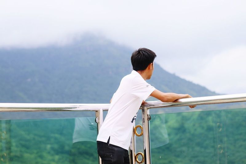 Side view of mid adult man looking at mountain while standing by railing against cloudy sky