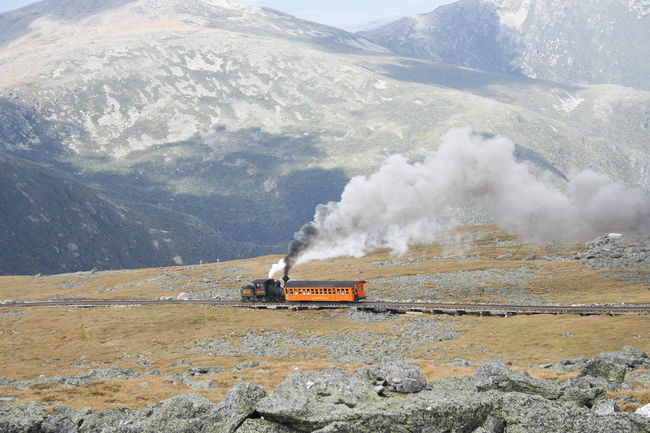 Steam Train of Mount Washington Cog Railway is pusing up Coach to the summit at good weather conditions Blue Sky White Clouds Bretton Woods Mount Washington Cog Railway Narrow Gauge Railway New Hampshire, USA Smoke Air Pollution Beauty In Nature Day Emitting Environment Land Vehicle Locomotive Mode Of Transportation Mountain Mountain Range Nature No People Non-urban Scene Outdoors Pollution Public Transportation Rail Transportation Smoke - Physical Structure Steam Train Summit Train Train - Vehicle Transportation
