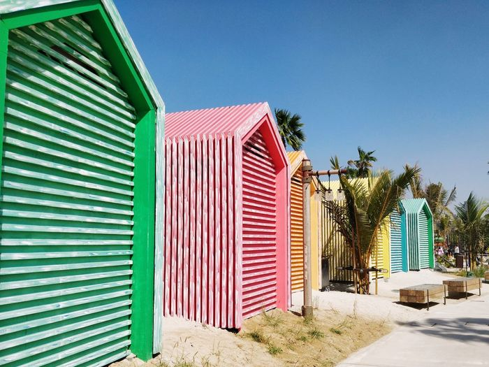 Multi colored beach huts against blue sky
