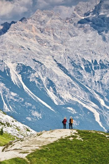 Rear view of people on snowcapped mountains