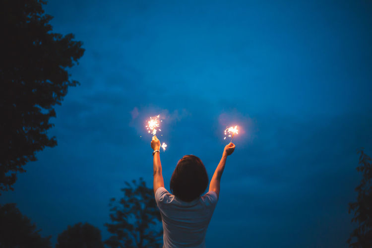 Rear view of woman with arms raised holding illuminated sparklers against sky